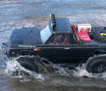 Mit mibenco Modellbau Farben schwarz lackiertes Modellauto fährt durchs Wasser
